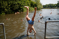© Licensed to London News Pictures. 21/06/2017. London, UK. People swim in Hampstead Heath Mixed Bathing Pond in north London as temperatures hit 34C and makes it the hottest UK June day since 1976 on Wednesday, 21 June 2017. Photo credit: Tolga Akmen/LNP