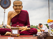 08 JANUARY 2015 - BANGKOK, THAILAND: A man meditates sitting next to a statue of a revered Buddhist monk on Sanam Luang. Buddhist in Bangkok have a chance to meditate in front of seven large statues of revered Buddhist monks and worship a hair relic of the Buddha at a series of altars on Sanam Luang near the Grand Palace in Bangkok.    PHOTO BY JACK KURTZ