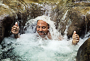 Man enjoys a refreshing water massage at Mayfield Falls, Glenbrook, Jamaica