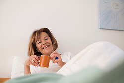 Senior woman in her bedroom drinking tea in the morning, Munich, Bavaria, Germany