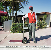 A gentleman Sky Cap stands in front of the terminal building at Santa Barbara Municipal Airport, California, USA. Wearing his red waste-coat, ID badge and cap he holds the handle of the baggage trolley with which he assists passengers to offload their belongings and guides them to the check-in counters inside. The man has a greying beard and sunglasses against the glare and is an eager helper to those struggling with heavy travel possessions. On the ground are stencilled the words 'Passenger Loading Only' referring to where departing travellers might seek help with baggage. There are armies of workers across the world keeping airlines and airports running 24/7. Picture from the 'Plane Pictures' project, a celebration of aviation aesthetics and flying culture, 100 years after the Wright brothers first 12 seconds/120 feet powered flight at Kitty Hawk,1903.