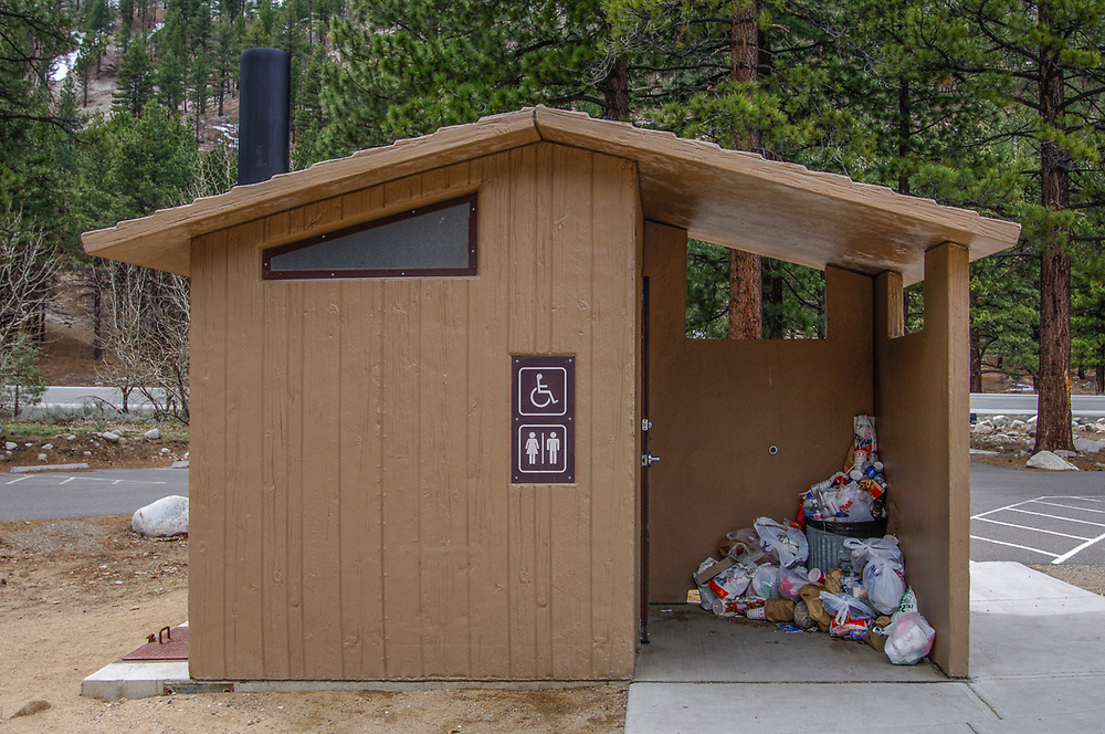 Pit toilet at a U.S. Forest Service recreation site, garbage overflow, April, Highway 395, eastern Sierra Mountains, California, USA