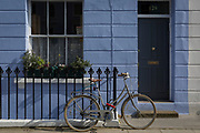 A ladies bicycle locked to the railings of a blue-painted in Holland Park W11 in the Royal Borough of Kensington and Chelsea, on 13th March 2018, in London, England.
