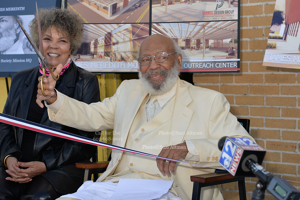 November 25, 2020 Jackson MS  Mississippi Pictured is James H. Meredith holding a big pair of scissors at the ribbon cutting for the future home of the  James Meredith Museum and Bible Society Headquarters as his wife Judy Alsobrooks Meredith looks on.  Native son and the first African American  American to attend the all white University of Mississippi, James Meredith cut a red, white and blue ribbon at the announcement for his Museum & Bible Society Mission HQ in Jackson Mississippi. The Meredith Museum and Bible Society HQ will house Meredith's archive of his 28 self published books, photographs and other artifacts of Merediths life, in addition to being a place where the teaching of Jesus Christ will be taught. It will also be a place where scholars can learn about Meredith, his life's work and his 3 missions from God. The first mission was for Meredith to destroy the white supremacy barrier at One Miss in 1962, the second Mission was to get Blacks to register to vote on his March Against Fear in 1966 and his 3rd Mission is to establish the Bible Society and Musem. Photos © Suzi Altman