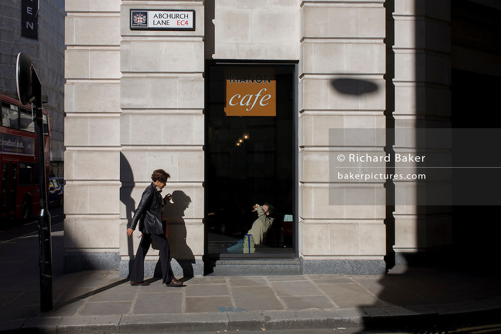 Passer-by and a City cafe in sunlight on Abchurch Lane in the City of London, the capital's financial district and oldest quarter.