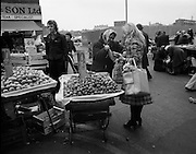 Moore Street, Dublin.      (J97)..1975..23.12.1975..12.23.1975..23rd December 1975..For well over a hundred years Moore Street has served the citizens of Dublin. The longest running open air fruit and vegatable market offers value for money,particularly to those where money is in short supply. Predominately a fruit and veg market there are several traders who sell fish and seasonal goods, as illustrated by the photographs showing turkeys and holly wreaths being sold on the run up to Christmas..At ten pence a pound, brussell sprouts proved to be a good seller at this time of year. Image shows a shopper having her bag filled by a street trader.