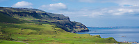 Green hillsides and rugged cliffs rise above Loch Na Keal, Isle of Mull, Scotland