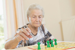 Senior woman playing board game in rest home, Bavaria, Germany