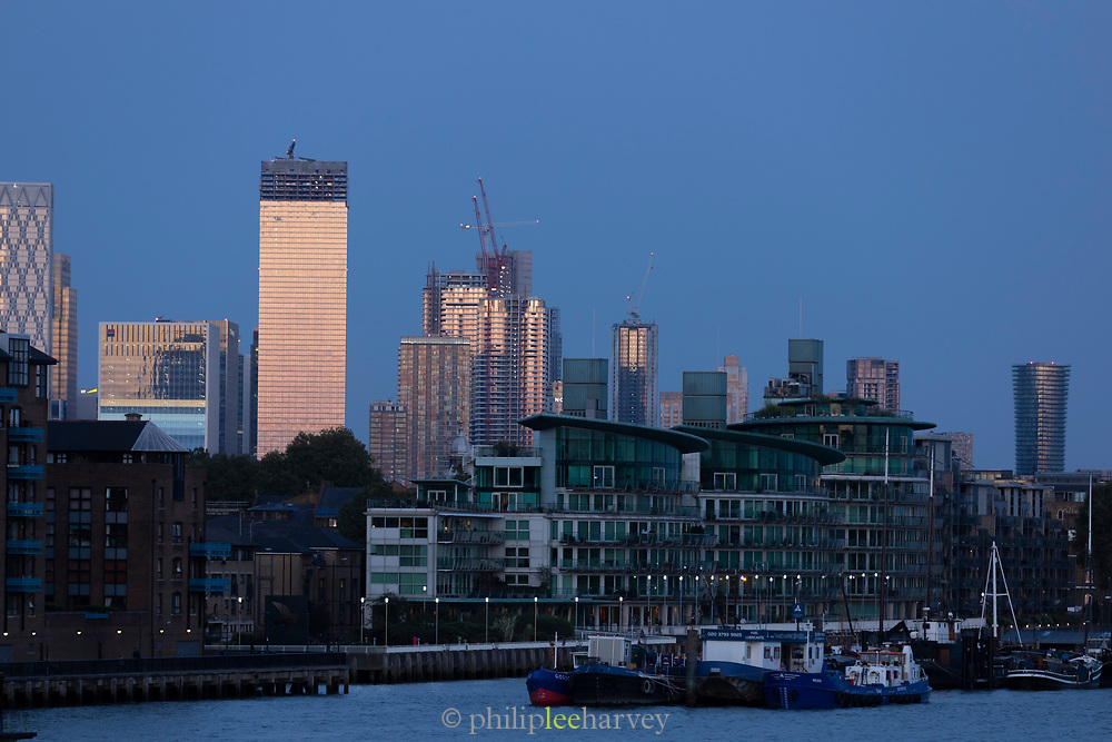 City skyline of Canary Warf with cranes at dusk, London, England, UK
