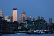 City skyline of Canary Warf with cranes at dusk, London, England, UK