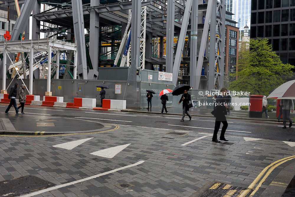 Businessmen with corporate umbrellas pass beneath a new construction project in London's financial district, the Square Mile.