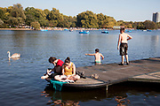 People out enjoying the unseasonally hot weather beside The Serpentine as a summertime heat wave hits London and the UK in what should be Autumn. Summer prolonged in a heatwave which results in a packed Hyde Park as families and friends try to soak up the last rays of sunshine and warmth in this Indian Summer.