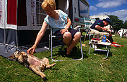 A husband, wife, child and their dog are caravan campers who are relaxing in chairs outside their caravan's awning. Their pet dog lies with its belly up relishing the attention of being tickled by its 'mother' while the man leans over to help his child with a toy. Their table has Sun cream and sun glasses showing us this is high summer at the site at Looe in Devon, England, run by the prestigious Caravan Club of Great Britain whose membership stands around 1 million members. Formed in 1907 the club boasts over 900 staff and an annual turnover of around £100 million. Rules about pitching vans and how to behave with waste, children and noise are strictly controlled and often, sites specialise more for families with kids or for older people wanting more peace.