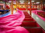"""29 MARCH 2017 - BANG KRUAI, NONTHABURI, THAILAND:  A Buddhist monk pulls back the sheet the represents people's ritualistic rebirth at Wat Ta Kien (also spelled Wat Tahkian), a Buddhist temple in the suburbs of Bangkok. People go to the temple to participate in a """"Resurrection Ceremony."""" Groups of people meet and pray with the temple's Buddhist monks. Then they lie in coffins, the monks pull a pink sheet over them, symbolizing their ritualistic death. The sheet is then pulled back, and people sit up in the coffin, symbolizing their ritualist rebirth. The ceremony is supposed to expunge bad karma and bad luck from a person's life and also get people used to the idea of the inevitability of death. Most times, one person lays in one coffin, but there is family sized coffin that can accommodate up to six people. The temple has been doing the resurrection ceremonies for about nine years.         PHOTO BY JACK KURTZ"""