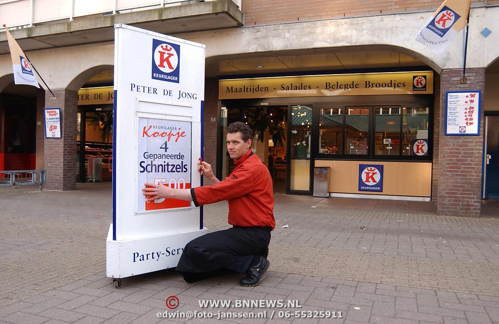 Slager Peter de Jong zet reclamebord buiten zijn winkel