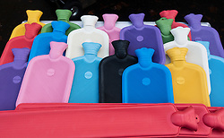 Traditional colourful rubber hot water bottles for sale at stall in weekend market in Berlin, Germany