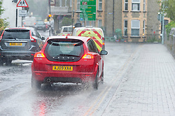 © Licensed to London News Pictures.28/07/2021. Builth Wells, Powys, Wales, UK. A motorist drives along a rainy street during a thunderstorm at Builth Wells in Powys, UK. Photo credit: Graham M. Lawrence/LNP