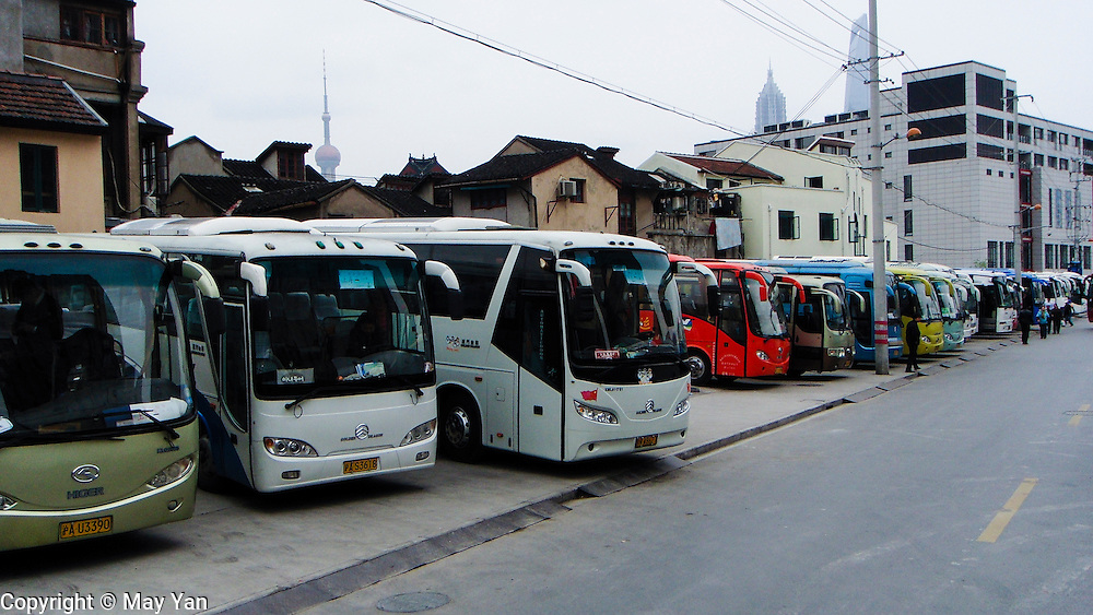 A long row of tourist buses sit parked on the outskirts of Shanghai, China.