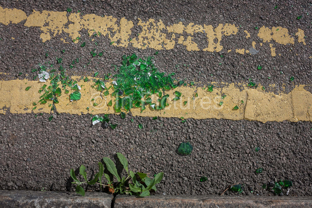Broken green glass lying in a pile on double-yellow lines in a south London gutter, on 2nd October September 2016, at the National Gallery, London, England.