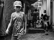 26 JANUARY 2018 - SANTO DOMINGO, ALBAY, PHILIPPINES: A boy evacuated from his home on the Mayon volcano walks past a row tents at Barangay Lidong shelter. The shelter is in school and all of the classrooms are already being used to house evacuees. Recent arrivals are living in tents on the school grounds. The volcano was relatively quiet Friday, but the number of evacuees swelled to nearly 80,000 as people left the side of  the volcano in search of safety. There are nearly 12,000 evacuees in Santo Domingo, one of the communities most impacted by the volcano. The number of evacuees is impacting the availability of shelter space. Many people in Santo Domingo, on the north side of the volcano, are sleeping in huts made from bamboo and plastic sheeting. The Philippines is now preparing to house the volcano evacuees for up to three months.      PHOTO BY JACK KURTZ
