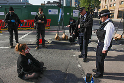 © Licensed to London News Pictures. 04/05/2020. London, UK. Members of environmental protest group Extinction Rebellion perform a sit in protest to prevent vehicles entering the HS2 site at Euston Station in London, to protest against the building of the HS2 rail project. The group have targeted HS2 sites across London. Photo credit: Marcin Nowak/LNP