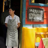 South America, Argentina, Buenos Aires. Parilla grill chef in doorway of La Boca restaurant.