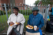 Clarence Road Hackney. Street tea party one week after the riots. Two elderly Caribbean ladies have tea and cakes .