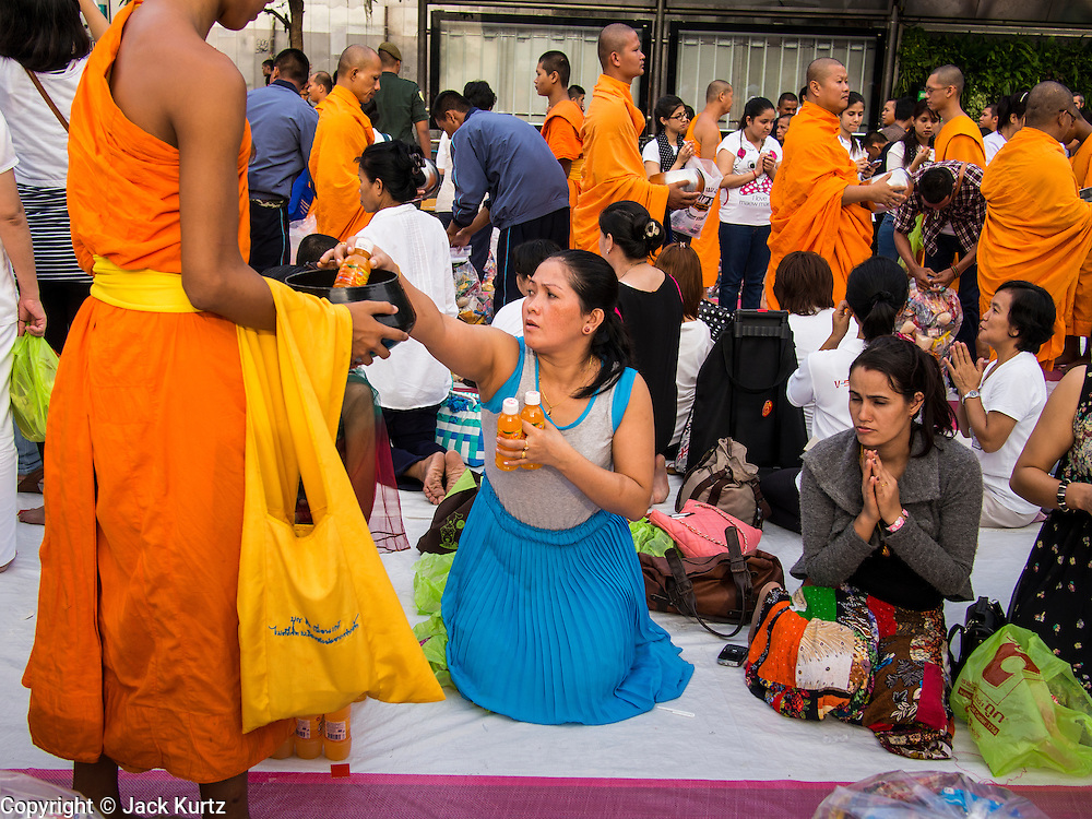 08 SEPTEMBER 2013 - BANGKOK, THAILAND:  A woman leans out to drop a donation into the alms bowl of a Buddhist monk during a mass alms giving ceremony in Bangkok Sunday. 10,000 Buddhist monks participated in a mass alms giving ceremony on Rajadamri Road in front of Central World shopping mall in Bangkok. The alms giving was to benefit disaster victims in Thailand and assist Buddhist temples in the insurgency wracked southern provinces of Thailand.      PHOTO BY JACK KURTZ