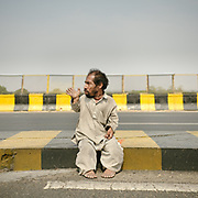 """Every day, Ajit walks from his village to the top of a slope on the highway, where trucks are forced to drive at a snail's pace. He waves, and the driver might just throw a coin to him out of the window.""""That's how I make my living, simple ... and nothing else,"""" he says.<br /> Uttar Pradesh Province."""