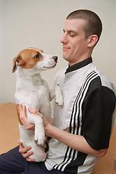 Resident of homeless hostel holding pet dog,