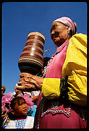 Girl eyes old Sakha woman with ritual cup of kumyss- fermented mare's milk; Ysyakh fest/Yakutsk Russia