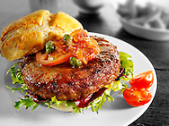 Beef burger in a bun with onion relish and salad