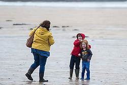 A mother and her daughters play on a cold, windy  day at Fistral Beach in Newquay, Cornwall.