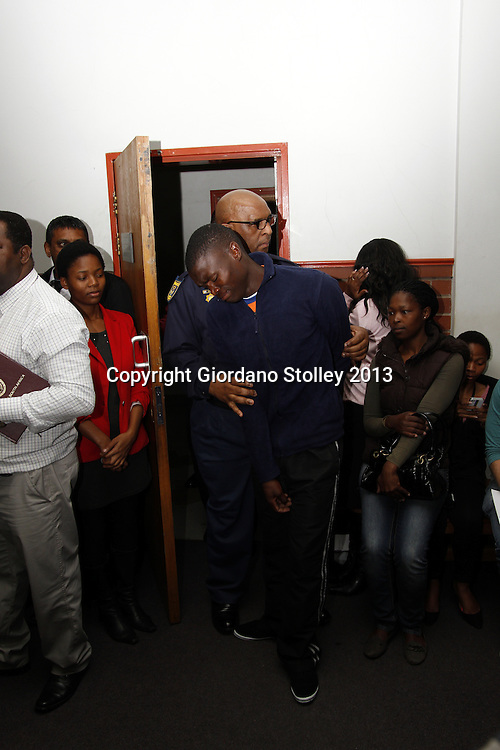 DURBAN - 9 September 2013 - A distraught Sanele Goodness May (centre), the driver of an articulated lorry that crashed into four minibus taxis and a car killing 22 people,  is escorted by a police officer into the Pinetown Magistrates Court. Sanele's lawyer Theasan Pillay was appointed by Sagekal Logistics, the company that owned the lorry he was driving. May faces 22 murder charges. Picture: Allied Picture Press/APP
