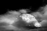 """Cumulonimbus clouds are tall and dense, and involved in thunderstorms and other intense weather. Cumulonimbus means """"column of rain"""" in Latin. They form as a result of atmospheric instability. These clouds can form alone, in clusters, or along a cold front in a squall line. They create lightning through the heart of the cloud. Cumulonimbus clouds form from cumulus clouds (namely from cumulus congestus) and can further develop into a supercell, a severe thunderstorm with special features."""