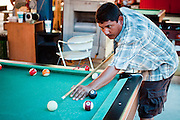 July 25 - PHOENIX, AZ: ARMANDO GUTIERREZ, originally from Mexico, plays pool at El Gran Mercado. El Gran Mercado (The Big Market) in Phoenix is the largest flea market in the Phoenix area and has served the area's immigrant community for more than 20 years. With more than 150 small independent stalls selling Mexican clothes, cowboy hats, Mariachi music and food stalls selling Mexican favorites like birria chivo (goat stew) and menudo (tripe) it was more like a Mexican market than an American mall. Business in the mercado is down more than half this year because many immigrant families, legal and illegal, are leaving Arizona before the state's tough new anti-immigrant law, SB 1070 goes into effect on July 29. SB 1070 allows local police officers to check the immigration status of people they have probable cause to believe may be in the US illegally and requires immigrants to carry their immigration papers with them at all times.    Photo by Jack Kurtz