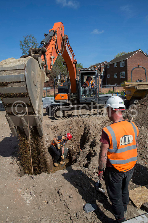 Builders use an orange JCB to lay drainage pipes in the ground around the foundations of a new build housing construction site in Norwich, Norfolk.  United Kingdom