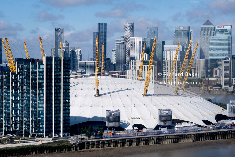 An aerial view from an Emirates Air Line cable car of showing Thames riverside apartments, the O2 Arena on the Greenwich Peninsular and the distant London Docklands, on 11th August 2021, in London, England.