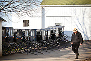 Amish man walks past parked horse buggies at a stable in Gordonville, PA.