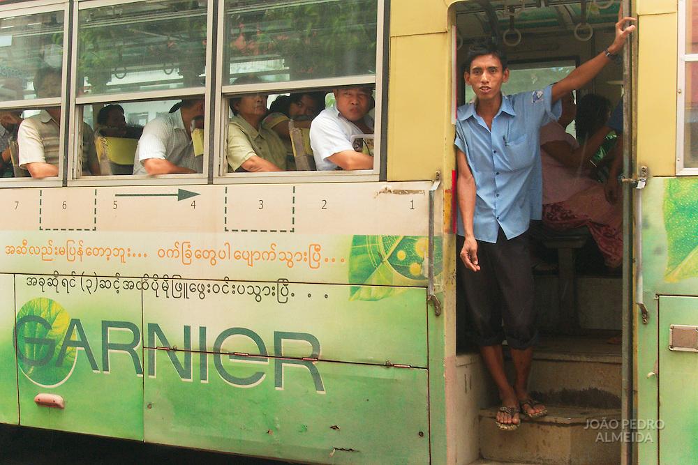 Boy standing at bus entrance at Yangon