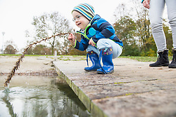Little boy crouching on a landing pier on lake holding branch into water with his mother in background