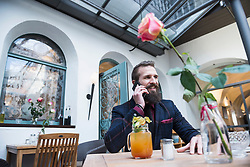 Young man using mobile phone while sitting at restaurant