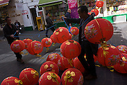 "Preparations in London's Chinatown for the mid-Autumn (also Lantern or Moon) Festival where paper lanterns are to hang. The Mid-Autumn Festival, also known as the Moon Festival or Zhongqiu Festival is a popular harvest festival celebrated by Chinese, Korean, and Vietnamese people, dating back over 3,000 years to moon worship in China's Shang Dynasty. It was first called Zhongqiu Jie (literally ""Mid-Autumn Festival"") in the Zhou Dynasty. In Malaysia, Singapore, and the Philippines, it is also sometimes referred to as the Lantern Festival or Mooncake Festival. The Mid-Autumn Festival is held on the 15th day of the eighth month in the Chinese calendar, which is in September or early October in the Gregorian calendar. It is a date that parallels the autumnal equinox of the solar calendar, when the moon is at its fullest and roundest."