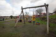 A young mother checks her mobile phone whilst pushing child on a swing on 11th January 2017 in London, United Kingdom. West Norwood community playground in South London. From the series Our Small World, an observation of our mobile phone obsessions