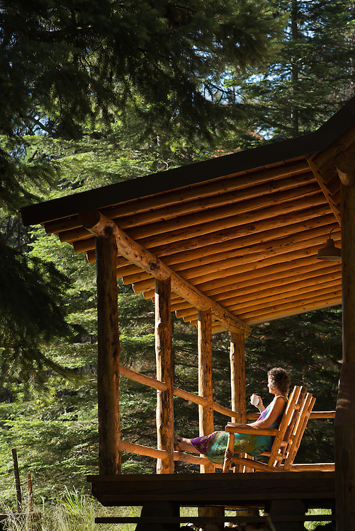 Woman enjoying a hot drink on the porch of a log cabin at the Minam River Lodge in Oregon's Wallowa Mountains.