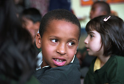 Primary school boy sitting on floor in school hall during assembly,