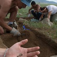 "Dr. William Fitzhugh unearths ancient charred bones in a 2700+ year-old, bronze age  ""khirigsuur"" burial mound at Ulaan Tolgoi archaeological site near Lake Erkhel, north of Muren, Mongolia.  Tsogtbayar Tsolmon (""Tsoomoo"") & Christie Leece background.  (Nick Wiltsie's hand)."