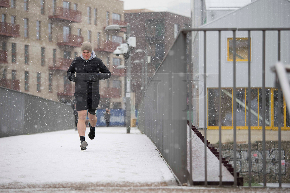 © Licensed to London News Pictures.24/01/2021, London,UK. Members of the public enjoy walk in snowy weather through Queen Elizabeth Olympic Park in east London as the third national lockdown continues. Photo credit: Marcin Nowak/LNP