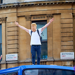 © Licensed to London News Pictures. 09/06/2018. LONDON, UK.  Protesters stand on the roof of a sightseeing bus in Trafalgar Square after a rally calling for the release of Tommy Robinson (aka Stephen Yaxley-Lennon) who was recently jailed for 13 months for contempt of court.   Photo credit: Cliff Hide/LNP