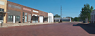 vacant brick street and brick buildings in a small west Texas village panorama